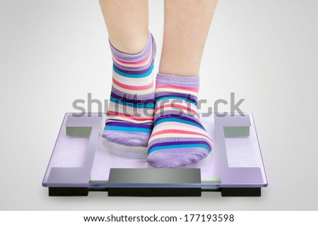 Woman feet on grey scales - stock photo
