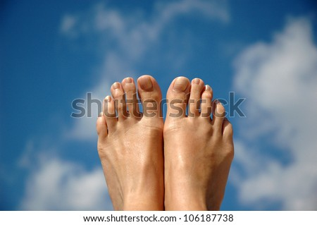 Woman feet on the sky background - stock photo