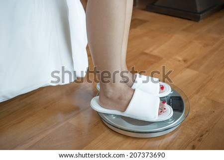 Woman feet on weight scale - stock photo