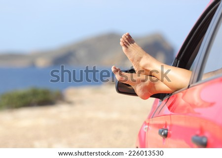 Woman feet relaxing in a car on the beach with the sea in the background - stock photo