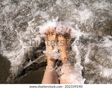 woman feet relaxing on the shore waiting for the wave - stock photo