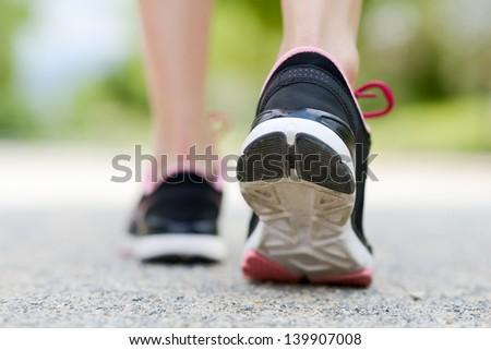 Woman feet running on road closeup on shoe - stock photo