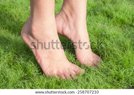 Woman feet tiptoe over green grass. - stock photo