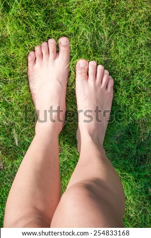 Woman feet walk over green grass. - stock photo