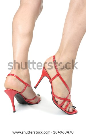 Woman feet wearing red high heels over white - stock photo
