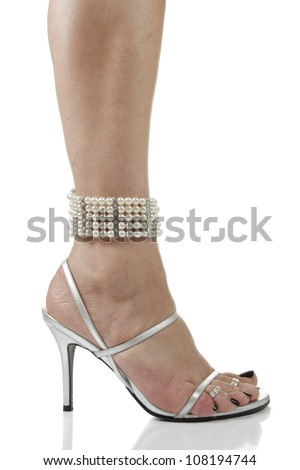 Woman feet wearing silver heel shoes and pearls over white background - stock photo