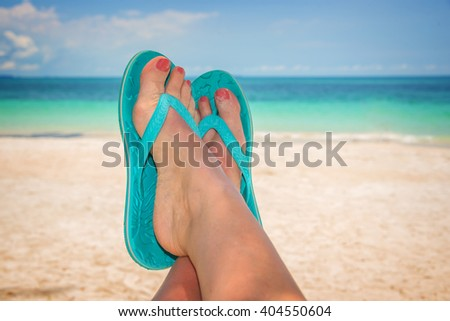 Woman feet with blue flip flops, beach and sea in the background - stock photo
