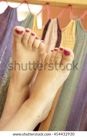 Woman feet with painted nails resting in a hammock