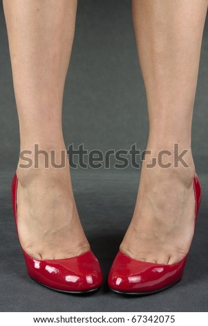 Woman feet with red high heels over grey