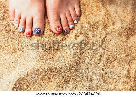 Woman feet with red toenails on natural beach sand - stock photo