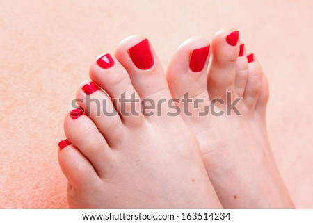 woman feet with red toenails on pink towel - stock photo