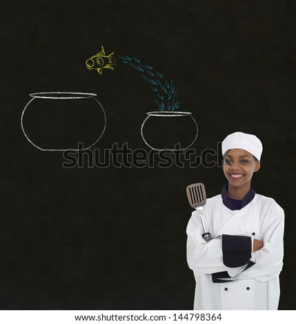 Woman female African or African American chef jumping fish decision on chalk blackboard background - stock photo