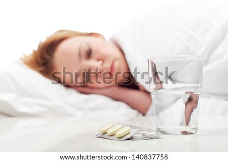 Woman fighting sickness with pills and resting - focus on medication - stock photo