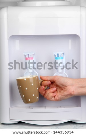 Woman filling cup at water cooler - stock photo