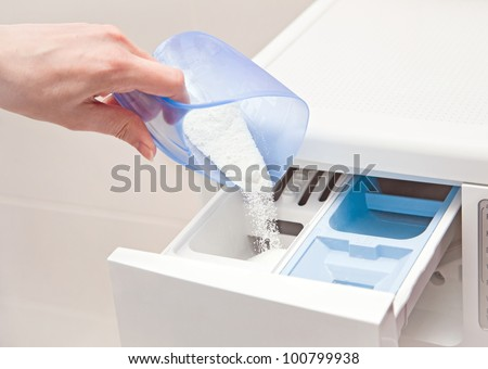woman filling detergent into the washing machine