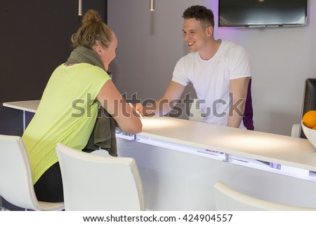 Woman filling in a registration form with help from man at a desk in health club