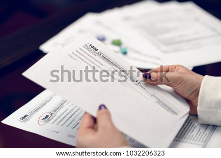 Woman fills the tax form, working with tax documents.Form 1040 Individual Income Tax return form. United States Tax forms 2017/2018.