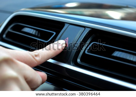 woman finger hitting car emergency light botton, man pressing red triangle car hazard warning button - stock photo