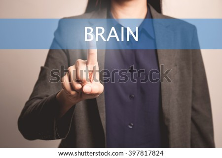 woman finger pointing at the camera with brain word - stock photo