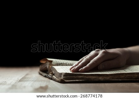 woman finger presses on old bible book in a dark room over wooden table and reading - stock photo