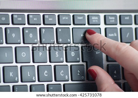 Woman finger  typing on laptop delete keyboard close up - stock photo