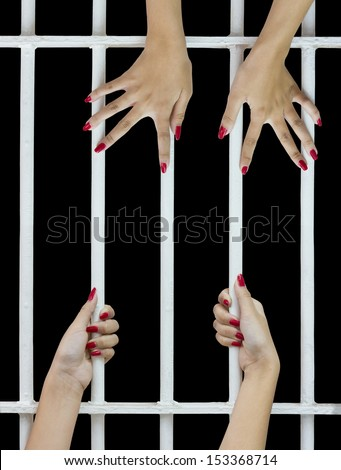 Woman fingers with red nails holding grip on the bars of the cage  - stock photo