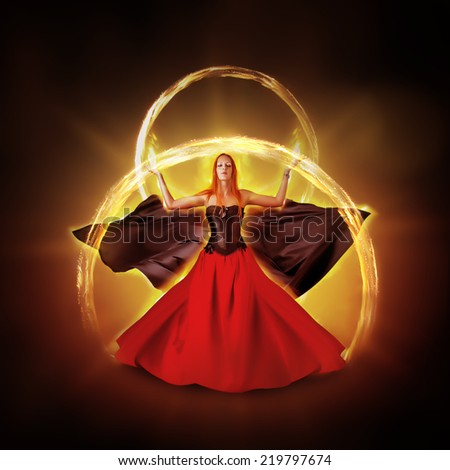 woman fire mage in medieval dress with developing mantle on black background - stock photo