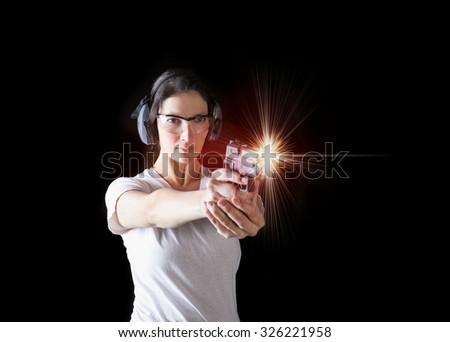 Woman firing a gun with protective gear - stock photo