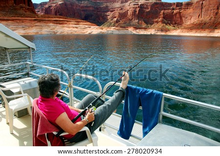 Woman fishes and enjoys view from a houseboat on Lake Powell. - stock photo