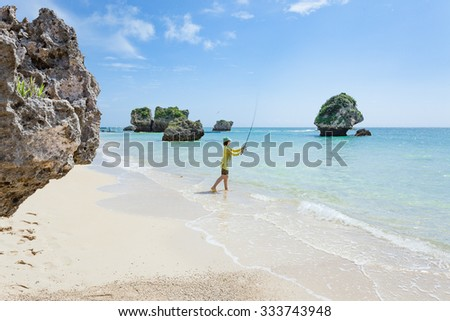 Woman fishing on white sand tropical beach with clear water of a coral lagoon, Okinawa, Japan - stock photo