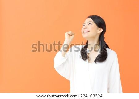 Woman fist pumped celebrating success - stock photo