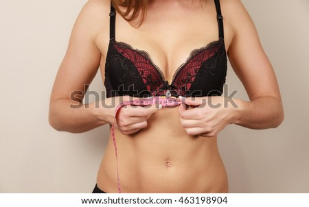 Woman fit girl in black bra lingerie with measure tape measuring her chest breasts. Closeup part of female body.