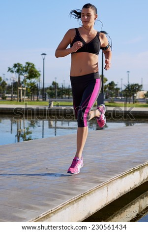woman fitness  jogging in park with earphones for music while she runs