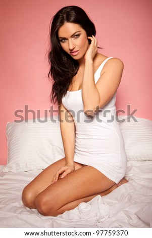 woman fixing her hair sitting on the bed with white sheets wearing a white tank top on pink background - stock photo