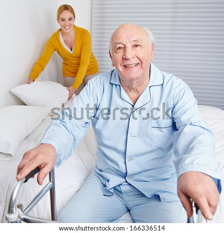 Woman fixing sheets of bed for senior citizen man in the family - stock photo