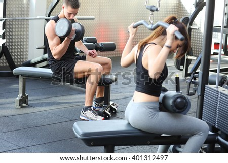 Woman flexing muscles in gym