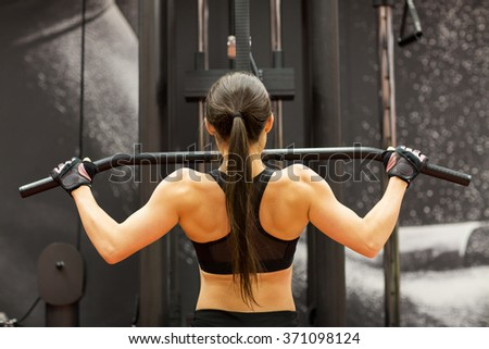 woman flexing muscles on cable machine in gym - stock photo