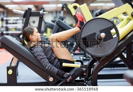 woman flexing muscles on leg press machine in gym - stock photo