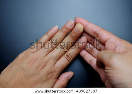 Woman flexing/stretching fingers against hand on blackboard background with light.