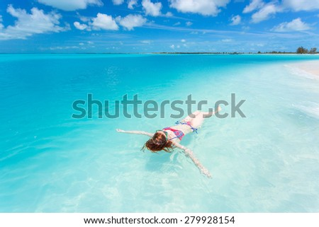 Woman floating and relaxing in turquoise waters at colorful tropical beach - stock photo