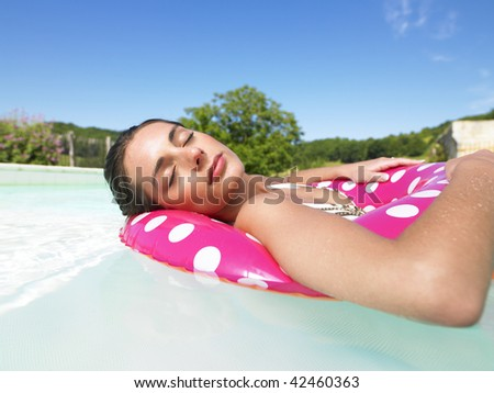 Woman floating in a pink polka dot inner tube with eyes closed. Horizontal. - stock photo
