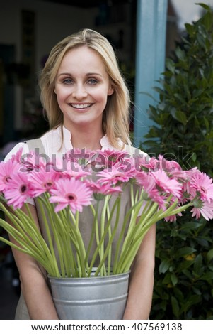 Woman florist or gardener holding a large pot of pink asters - stock photo