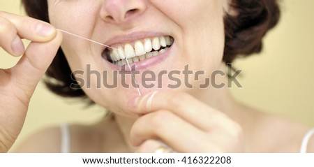 Woman flossing her teeth at home - stock photo