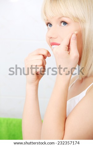 Woman flossing teeth with dental floss. - stock photo