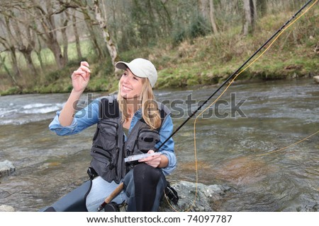 Woman fly-fishing in river - stock photo