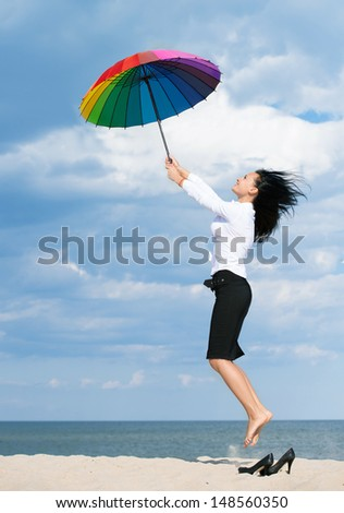 Woman flying away from her business problems with a colorful umbrella - stock photo