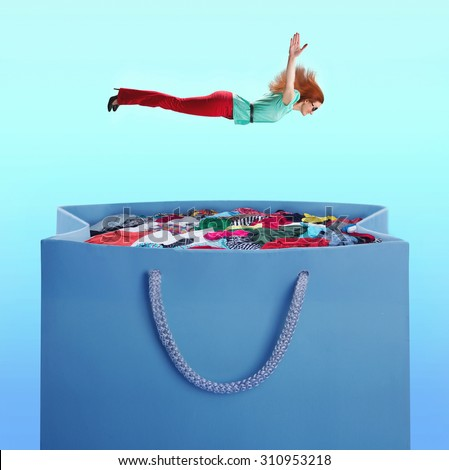 Woman flying to the heap of clothes - stock photo