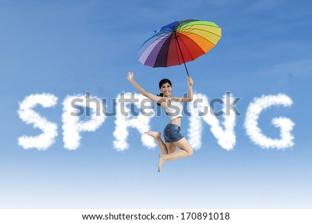 Woman flying with colorful umbrella in the spring word - stock photo