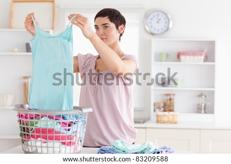 Woman folding clothes in a utility room - stock photo