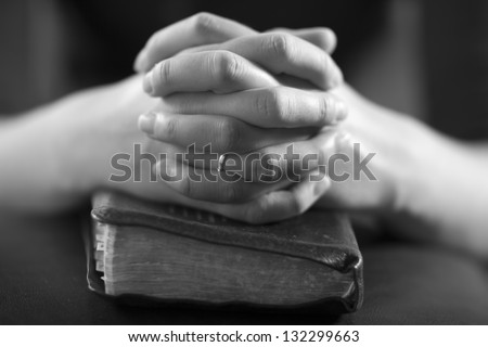Woman folding hands over her bible and praying to God.